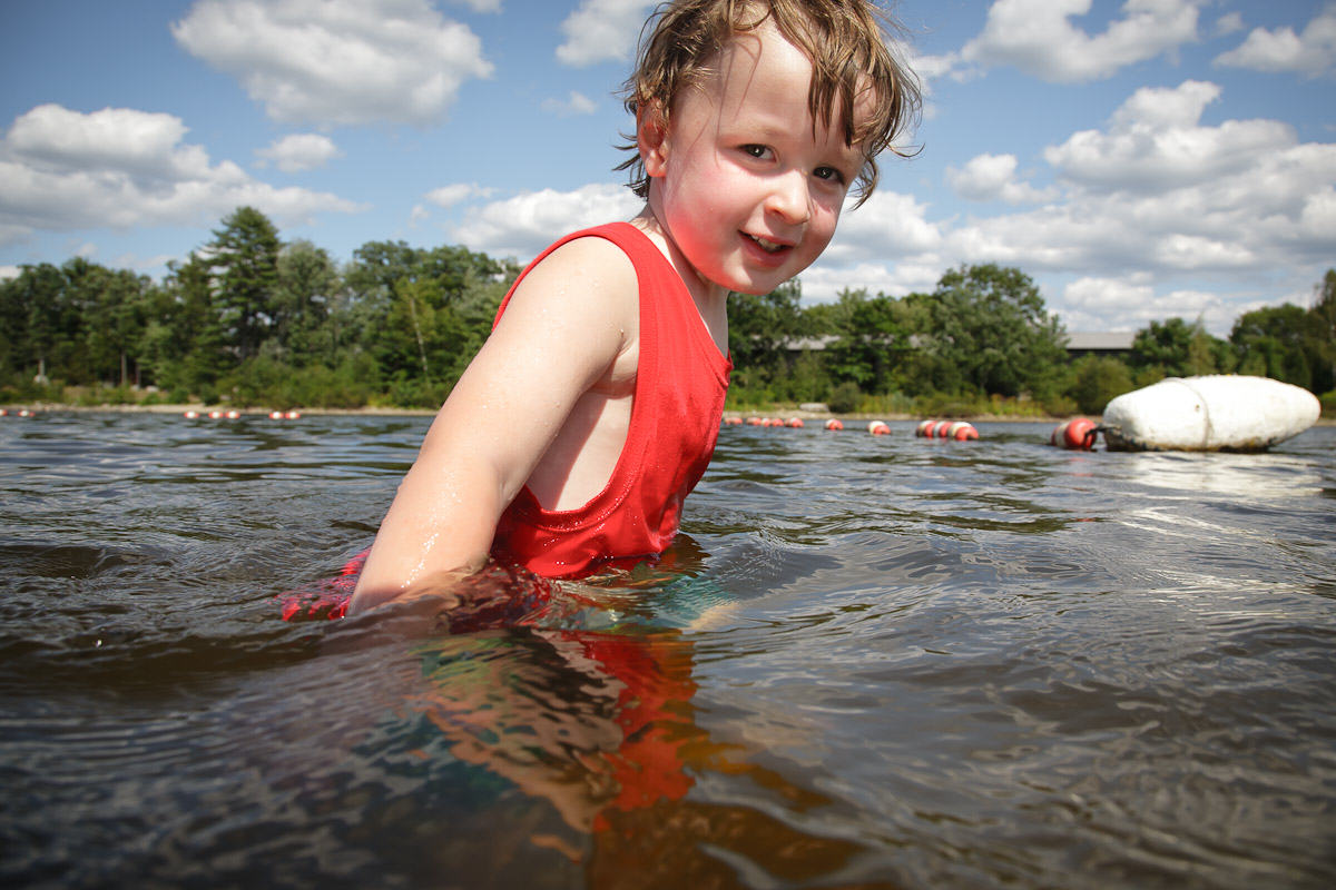 boy in pond swimming.